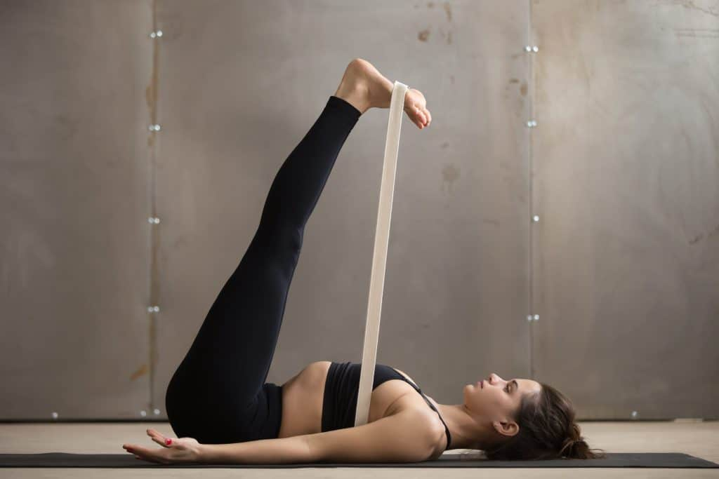woman doing legs up the wall with a yoga strap