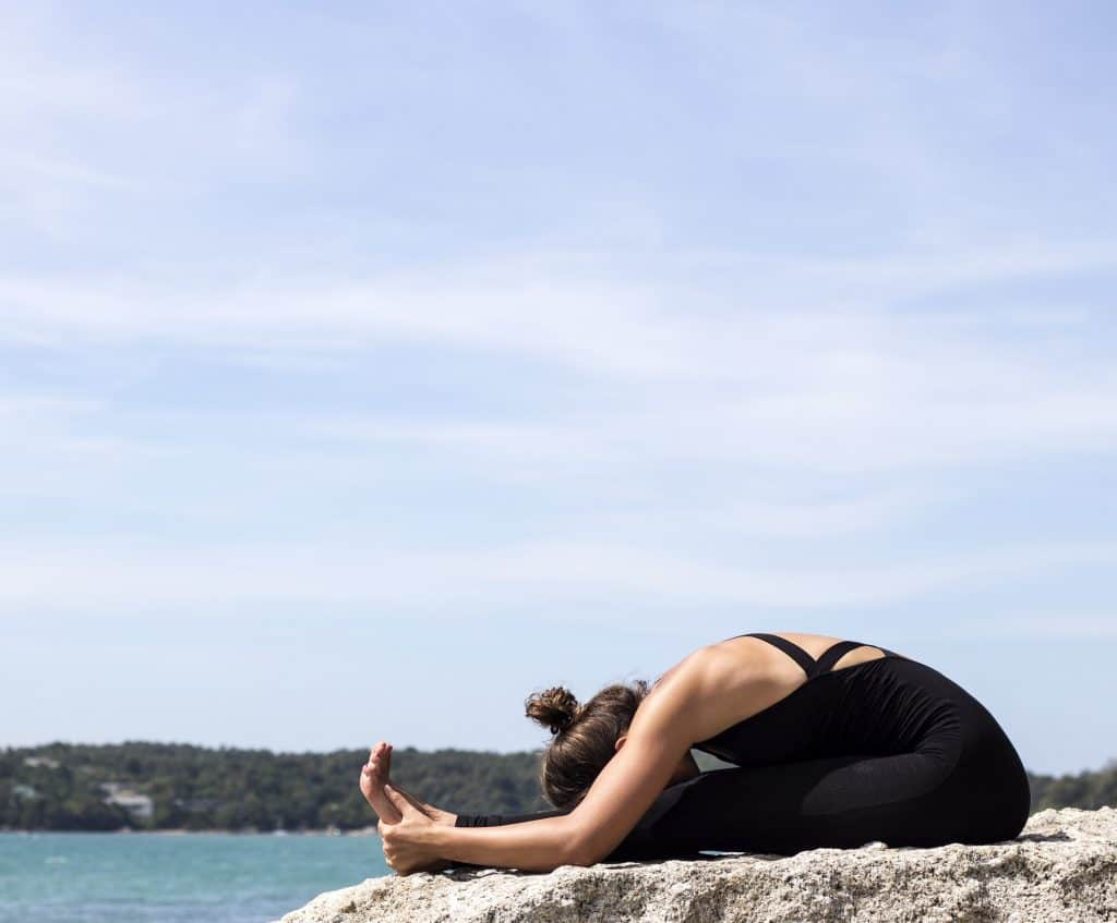 woman doing seated forward fold yoga pose